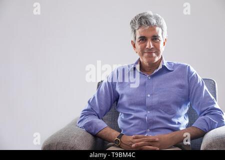 Retrato de altos hombre sentado en el sofá Imagen De Stock