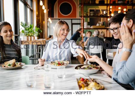 Feliz joven mostrando anillo de compromiso a amigos en la mesa de restaurante Imagen De Stock
