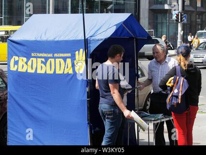 La gente se levanta al lado de una tienda de campaña electoral de la extrema derecha Svoboda (Libertad), partido político en Kiev.Las primeras elecciones parlamentarias tendrán lugar en Ucrania el 21 de julio de 2019. Según las encuestas de opinión, en el 2019 las elecciones parlamentarias de Ucrania 5 Partes será capaz de entrar en el Parlamento ucraniano : El presidente ucraniano Volodymyr Zelensky's partido llamado siervo del pueblo con 41,5%, pro-ruso de la oposición - Plataforma de por vida con el 12,5%, la parte de voz de estrella de rock ucraniano Svyatoslav Vakarchuk con 8,8%, solidaridad europea del ex presidente ucraniano, Petro Poroshenko con Imagen De Stock