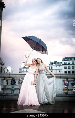 Retrato de dos modelos femeninos sosteniendo un paraguas, Trafalgar Square, Londres, Reino Unido. Imagen De Stock