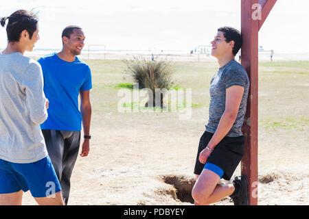 Los corredores macho descansando, hablando en sunny park Imagen De Stock
