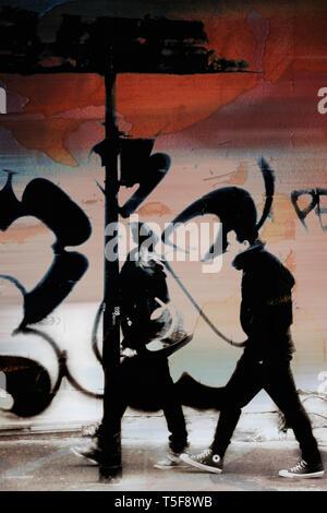 Una pareja joven camina en el barrio árabe Barbes en París y pasa el graffiti. Imagen De Stock
