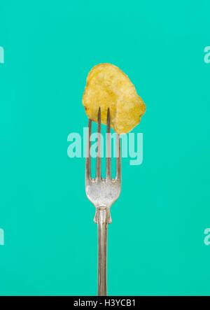 Uno de patatas fritas en la bifurcación. Cerca de aperitivos salados y grasas. Concepto de una alimentación Imagen De Stock