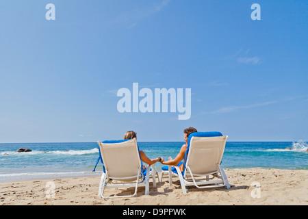 Vista trasera de la pareja en las sillas de playa Imagen De Stock