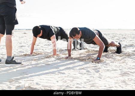 Los hombres haciendo push-ups en sunny beach Imagen De Stock