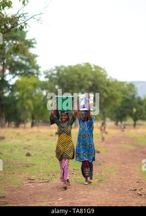 Tribu Peul niñas llevando cubos llenos de agua en la cabeza, distrito Savanes, Boundiali, Costa de Marfil Imagen De Stock