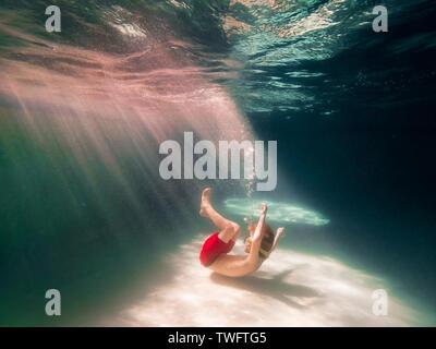 Boy enroscada sobre el fondo de una piscina Imagen De Stock