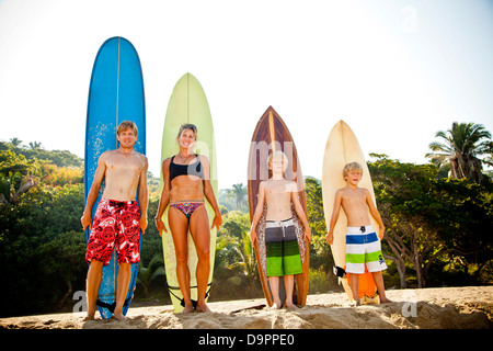 Una familia de cuatro, de pie en frente de las tablas de surf Imagen De Stock