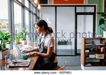 Cafe dueño trabajando en equipo portátil Imagen De Stock