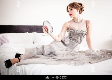 Mujer joven en vestido de noche mirando a sí misma en el espejo mientras recostado sobre la cama Imagen De Stock