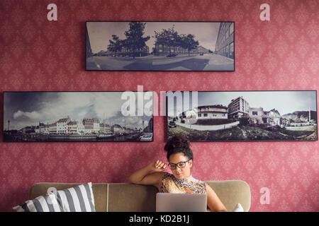 Hermosa mujer sentada en un sofá y utilización portátil Imagen De Stock