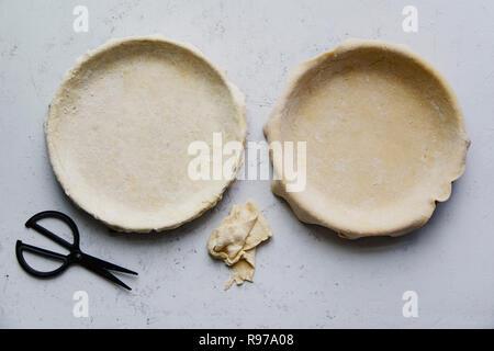Las materias crudas y corteza de tarta en un molde para hornear durante dos tartas del fondo de hormigón Imagen De Stock