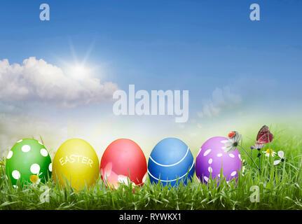 Los huevos de Pascua, teñido, con un patrón en el fondo de un cielo soleado en el césped Imagen De Stock
