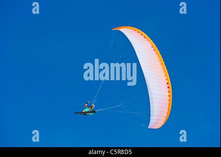Un piloto de parapente sonríe como hace hace un rápido giro bancarizado. Imagen De Stock