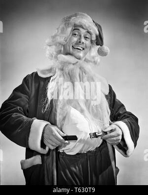 1950 El hombre sonriente VESTIRSE EN SANTA TRAJE sosteniendo la correa acolchada alrededor del estómago - x2535 RCH001 HARS BARBA 1 PAZ COMPLACE ALEGRÍA CELEBRACIÓN CORREA LIFESTYLE STUDIO SHOT PERSONA CLAUS HOME vida ejemplar espacio icono media longitud sabia inspiración personaje masculino SAN B&W contacto ocular iconos ocupación pelos felicidad alegre sabiduría estómago simbolismo WHISKER CARACTERES ESPECIALES DE SANTA CLAUS OCASIÓN GENTE PERSONAJES SAN NICOLÁS SAN NICK Ocasión Especial traje rojo VIEJO SAN NICK RECHONCHO HASTA EL VELLO FACIAL VACACIONES OCUPACIONES SONRISAS STOUT DICIEMBRE VACACIONES DE NAVIDAD SANTA'S HELPER NICK DICIEMBRE 25 piel blanca Imagen De Stock