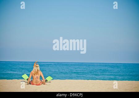 Mujer vistiendo nadar aletas sentado en la playa Imagen De Stock