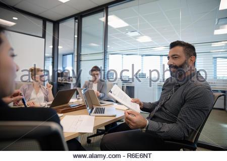 Empresario con papeleo hablando en la sala reunión Imagen De Stock