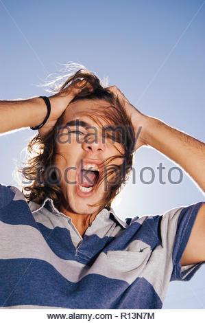 Un adolescente enojado bajo un cielo azul Imagen De Stock