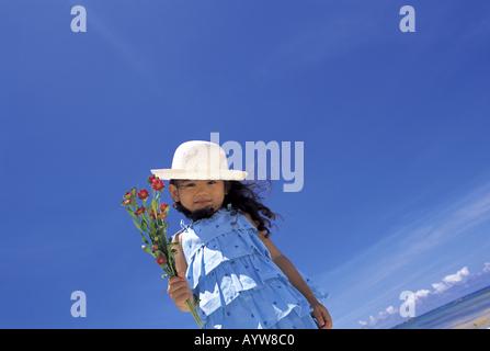 Vestida con un sombrero de paja con flores. Imagen De Stock