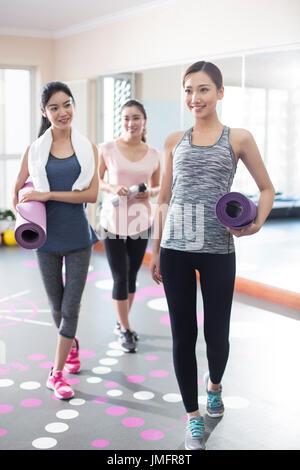 Las mujeres jóvenes con colchonetas para yoga en el gimnasio Imagen De Stock