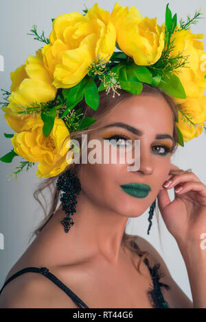 Retrato de una hermosa rubia con brillantes de maquillaje y un aro de flores amarillas Imagen De Stock