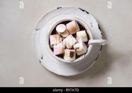 Taza de cerámica de chocolate caliente con malvavisco s'mores en platillo sobre tabla de mármol blanco. Bebida de invierno. Espacio laical, plana Imagen De Stock