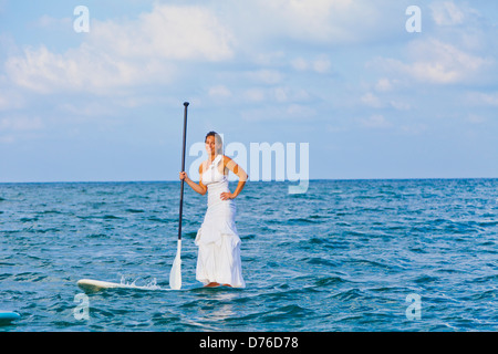 Mujer en vestido blanco caballo paddle board Imagen De Stock