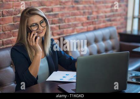 Mujer de negocios sentada en la mesa hablando por teléfono Imagen De Stock