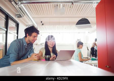 Hombre y dos mujeres que trabajan en la oficina, mujer de pie por la ventana en segundo plano. Imagen De Stock