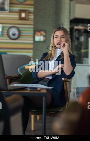 Una hermosa joven mira por la ventana cuidadosamente. Linda chica sentada en un cafe en un día soleado. Imagen De Stock