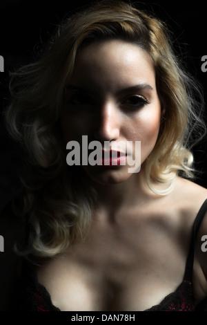 La expresión en el rostro de una joven y bella mujer rubia shot en suaves luces y sombras. Imagen De Stock