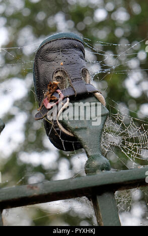 Zapata del niño empalado en baranda metálica spike Imagen De Stock