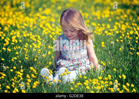 Una niña de 3 años de edad está sentado en un prado de flores Imagen De Stock