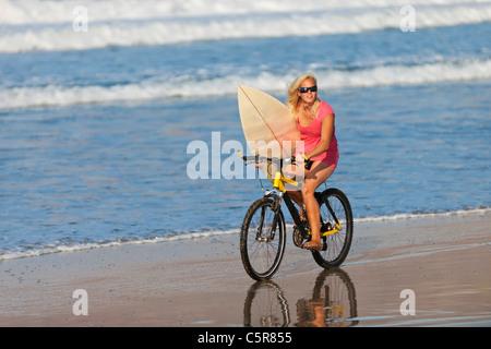 Un surfista montando una bicicleta de montaña con el mar. Imagen De Stock