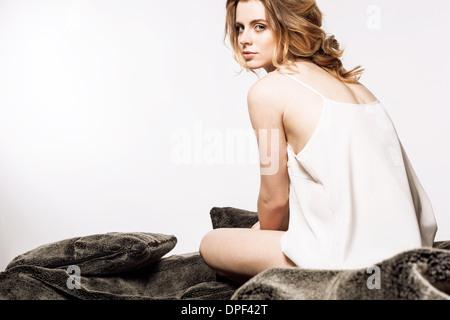 Mujer sentada en la cama Imagen De Stock