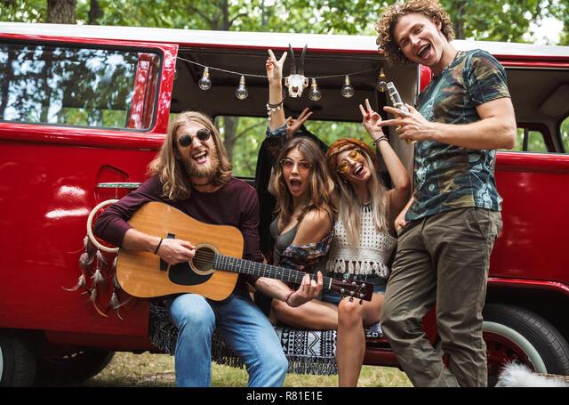 Grupo de jóvenes hippies que hombres y mujeres tengan diversión y tocando  la guitarra cerca de vintage minivan en la naturaleza Fotografía de stock -  Alamy