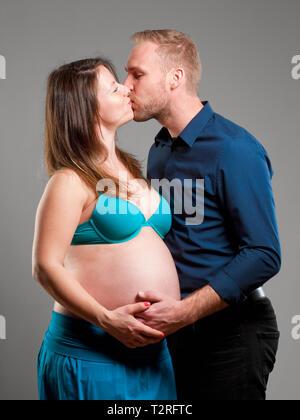 Femme enceinte avec son homme s'embrassant. Photo Stock