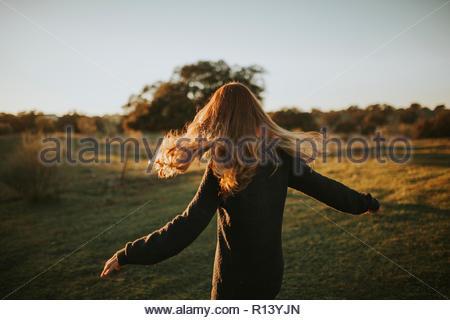 Vue arrière d'une femme aux cheveux longs qui se tient debout dans un champ sur une journée ensoleillée Photo Stock