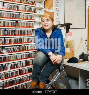 Femme assise sur l'échelle en entrepôt Photo Stock