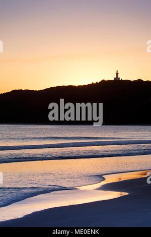 Silhouette de phare de Cape Byron et soleil, plage au coucher du soleil à Byron Bay en Nouvelle Galles du Sud, Australie Photo Stock