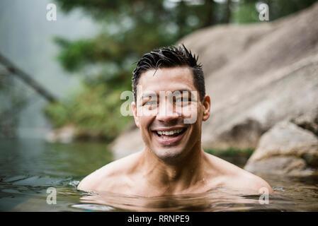 Portrait souriant, beau jeune homme nager dans le lac Photo Stock
