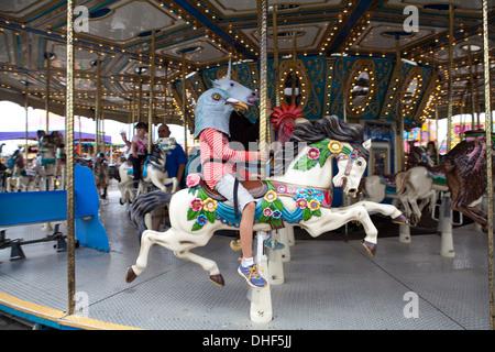 Les enfants portant des masques d'animaux à cheval sur un carrousel ride at state fair. Photo Stock