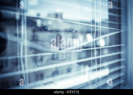 Old man looking out of window through blinds. Concept de l'observation et la surveillance de voisinage. Sentiment Photo Stock