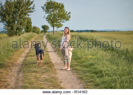 Tourné sur toute la longueur d'une femme debout avec ses chiens dans un champ Photo Stock