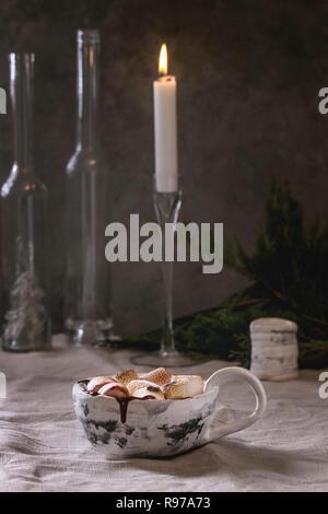 Tasse en céramique de chocolat chaud avec de la guimauve sur s'mores linge gris tapis de table. Boisson d'hiver. Photo Stock