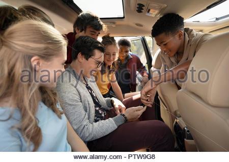Les adolescents à l'aide de smart phone in car Photo Stock