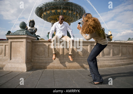 African woman taking photograph of boyfriend Photo Stock