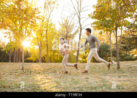 Happy young couple running in autumn woods Photo Stock