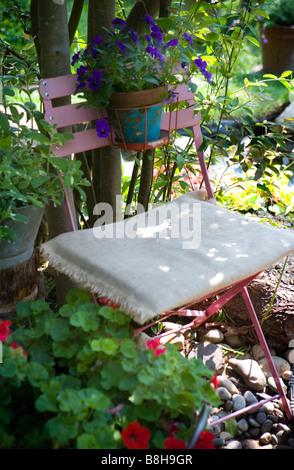 Chaise de jardin en métal rouge avec des pensées dans un pot Photo Stock