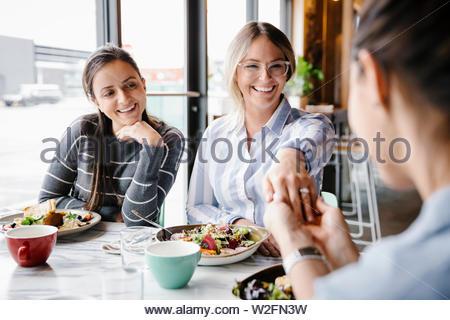 Happy young woman showing bague de fiançailles à des amis pour le déjeuner dans le café Photo Stock